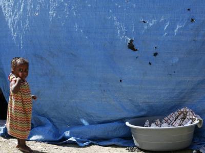 Ein kleiner Junge blickt in einem Auffanglager in Leogane in die Kamera eines Fotografen.