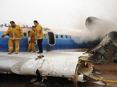 Feuerwehrleute auf dem Wrack der verunglückten Maschine im Iran.