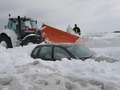 Feuerwehrmänner von der Freiwilligen Feuerwehr Altenkirchen auf der Insel Rügen und ein Traktorfahrer befreien auf der Halbinsel Wittow bei Kap Arkona ein Auto aus einer Schneewehe.