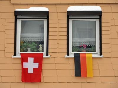Eine deutsche und eine Schweizer Flagge an den Fenstern eines Hauses.