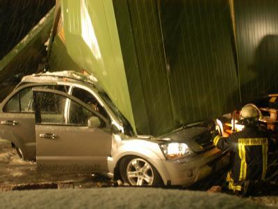 Ein Auto ist unter einem Teil der eingestürzten Firmenhalle begraben.
