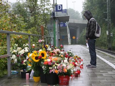 Ein Jugendlicher steht am Tatort vor niedergelegten Blumen.