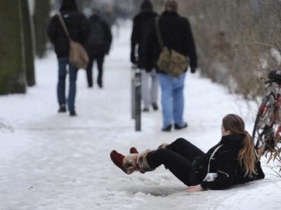Eine Passantin liegt in Hamburg auf dem Boden, nachdem sie auf dem rutschigen Boden ausgerutscht ist. Der Frost hat am Donnerstagmorgen zu vielen Einsätzen von Polizei und Feuerwehr auf Hamburgs Straßen geführt.