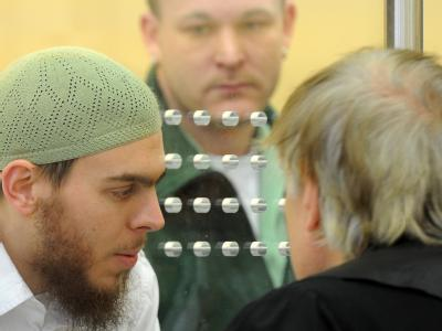 Der Angeklagte Daniel Schneider spricht durch eine Glasscheibe mit seinem Anwalt Bernd Rosenkranz.
