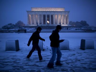 Passanten kämpfen vor dem Lincoln Memorial in Washington gegen den Wind an.