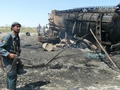 Ein afghanischer Polizist steht nach dem vom deutschen Oberst Klein angeordneten Luftangriff vor einem der ausgebrannten Tanklastzüge. (Archivfoto vom 04.09.2009)