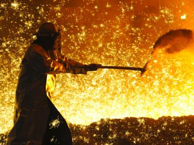 Ein Metallarbeiter vor einem angestochenen Hochofen.