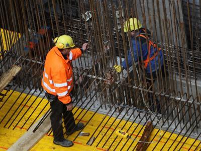 Arbeiter befestigen im Bauschacht Stahlträger.
