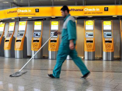 Ein Putzmann wischt am Flughafen von Frankfurt am Main den Boden.