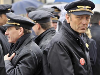Im strömenden Regen nehmen Piloten der Lufthansa am Flughafen in Frankfurt am Main an einer Protestkundgebung teil.