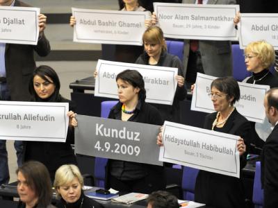 Die Linksfraktion hält im Bundestag Plakate mit den Namen der bei dem Angriff auf zwei Tanklastzüge getöteten Personen hoch.