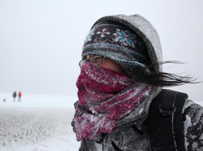 Mit einem Schal schützt sich bei Schneetreiben eine Spaziergängerin am Strand von in St. Peter-Ording gegen die Kälte.