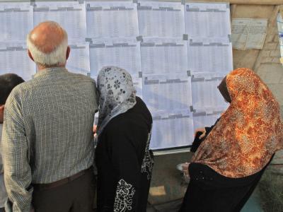 Iraker suchen ihre Namen auf ausgehängten Wählerlisten.