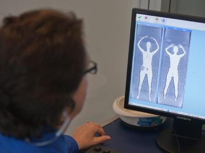 Eine Mitarbeiterin der Flughafensicherheit in Boston schaut auf ihrem Monitor auf die Figur einer Frau, die von einem Ganzkörperscanner durchleuchtet wurde (Pressevorführung).