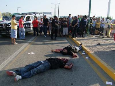 Schaulustige stehen neben den Leichen von zwei Männern in Acapulco.