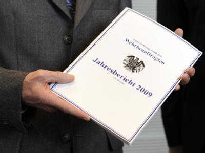 Bundestagspräsident Norbert Lammert zeigt den Jahresbericht des Wehrbeauftragten.