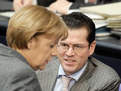 Bundeskanzlerin Merkel und Verteidigungsminister zu Guttenberg (CSU) unterhalten sich im Bundestag. Guttenberg steht wegen der Kundus-Affäre verschärft in der Kritik.