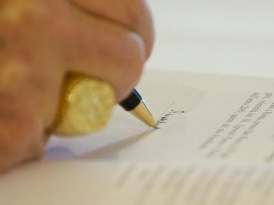 Papst Benedikt XVI. beim Unterschreiben (Archivfoto vom 07.07.2009).