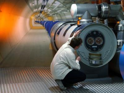 Ein Mitarbeiter des europäischen Teilchenforschungszentrum CERN bei Genf betrachtet ein Modell des LHC-Tunnels.