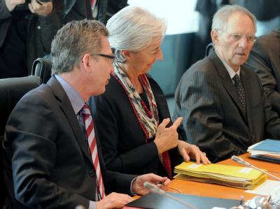 Innenminister de Maiziere (r) unterhält sich bei der Kabinettssitzung in Berlin mit der französischen Finanzministerin Christine Lagarde und Finanzminister Schäuble (CDU).