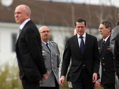 Verteidigungsminister Karl-Theodor zu Guttenberg (M) vor seinem Abflug vom Bundeswehrkrankenhaus in Koblenz, wo er die verwundeten Soldaten besucht hatte.