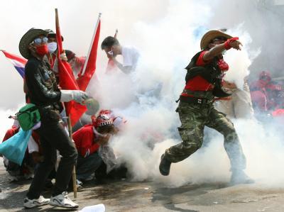 Ein Regierungsgegner wirft eine Gasgranate der Polizei zurück.