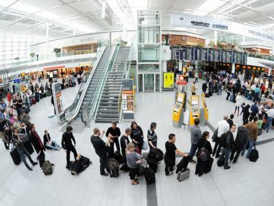 Menschen warten vor den Schaltern am Münchner Flughafen.