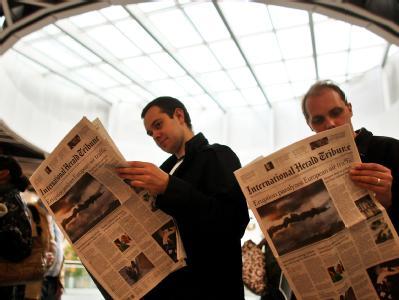 Ausländische Fluggäste lesen in einer Warteschlange im Terminal des Flughafens Düsseldorf die Berichterstattung über die Aschewolke.