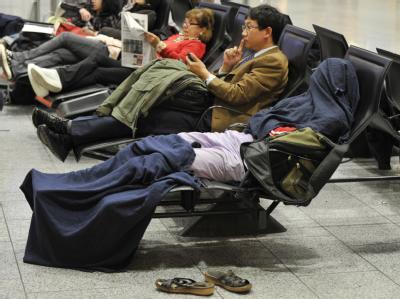 Von Kopf bis Fuß in Decken gewickelt warten gestrandete Passagiere auf eine mögliche Wiederaufnahme des Flugverkehrs.