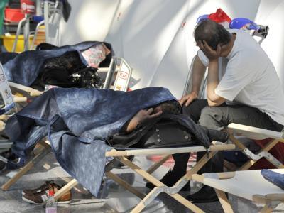 Auf Feldbetten warten erschöpfte Passagiere auf dem Flughafen in Frankfurt am Main auf Neuigkeiten von ihren Airlines.