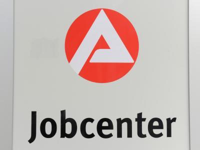 Blick auf das Logo der Arbeitsagentur am Eingang eines Jobcenters.