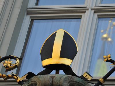 Das Kreuz des Doms spiegelt sich in Augsburg in einem Fenster am Bischofspalais.