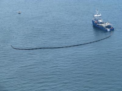 Ein Schiff versucht die drohende Ölpest im Golf von Mexiko einzudämmen.