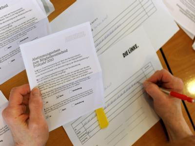 Mitarbeiter der Linkspartei zählen die Stimmzettel der Mitgliederbefragung aus.
