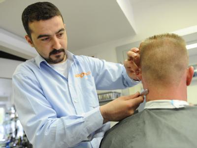 Der Friseur Baris Ince bedient in einem türkischen Friseursalon in Hannover einen Kunden.