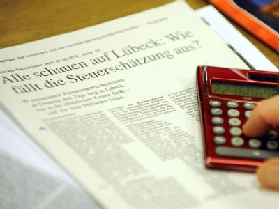 Ein Mitglied des Arbeitskreises Steuerschätzung tippt im Rathaus von Lübeck auf den Tasten seines Taschenrechners.