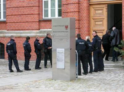 Polizeibeamte sichern zum Prozessbeginn um einen tödlichen Schuss eines Berliner Polizisten den Eingang am Landgericht Neuruppin (Brandenburg).