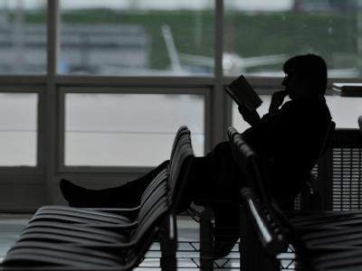 Ein Passagier sitzt im Abflugbereich des Münchner Flughafens.