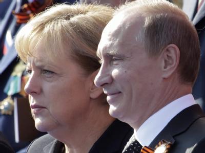 Kanzlerin Merkel und Russlands Ministerpräsident Putin beobachten die Militärparade in Moskau zum Gedenken an den Sieg über Deutschland 1945.