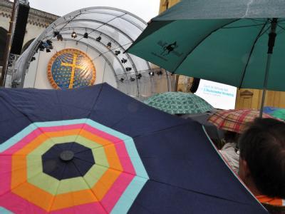 Gläubige verfolgen mit Regenschirmen die zentrale Ökumenische Feier zum 2. Ökumenischen Kirchentag.