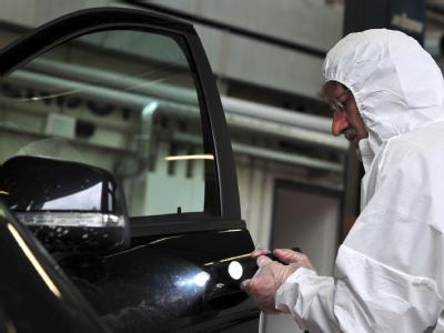 Ein Kriminaltechniker untersucht die Fahrertür des gefundenen Autos.
