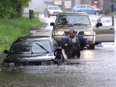 Ein Mann versucht sein Auto auf einer überfluteten Straße in Tschechien zu retten.