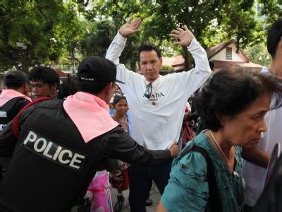 Ein Oppositionellerhat sein rotes Hemd abgelegt und ergibt sich bei der Tempelräumung der Polizei.