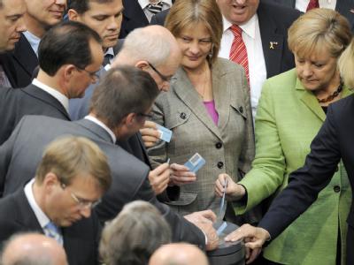 Bundeskanzlerin Merkel stimmt im Plenarsaal des Bundestages über das Finanzpaket ab.