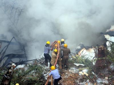 Feuerwehrmänner versuchen, das brennende Wrack zu löschen.