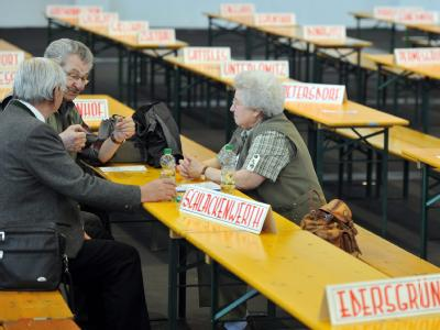 Drei Teilnehmer sitzen im Messezentrum Augsburg an Biertischen, auf denen Schilder mit Ortsnamen aus dem Sudetenland stehen.