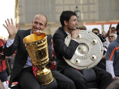 Bayern-Kapitän Mark van Bommel (r.) trägt die Meisterschale, Arjen Robben den DFB-Pokal.