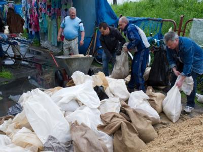 Händler eines Marktes in Slubice versuchen, mit Sandsäcken ihre Stände zu schützen.