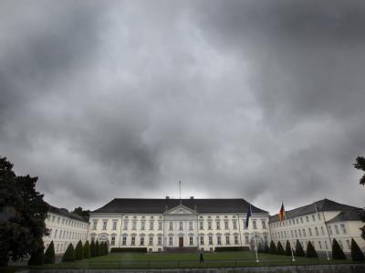 Dunkle Wolken ziehen über das Schloss Bellevue in Berlin hinweg.