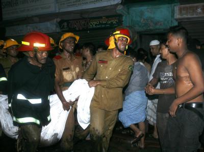 Feuerwehrleute tragen ein Opfer der Brandkatastrophe vom Ort des Unglücks.